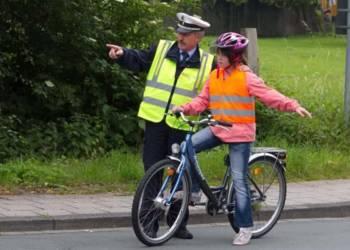 Ein Polizist weist ein Mädchen bei der Fahrradprüfung ein