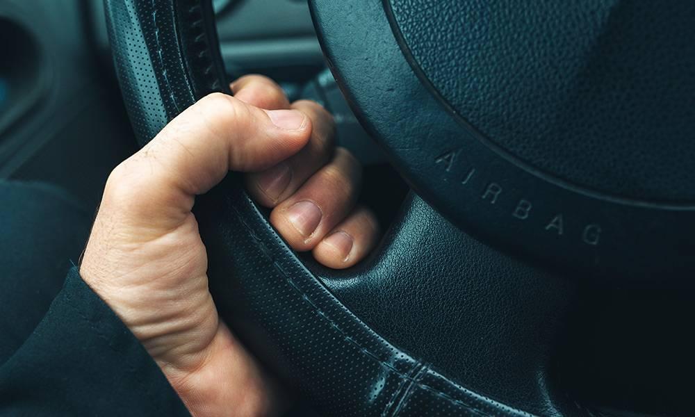 Eine männliche Hand am Lenkrad