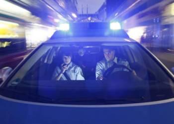 Streifenwagen fährt mit Blaulicht durch die Stadt