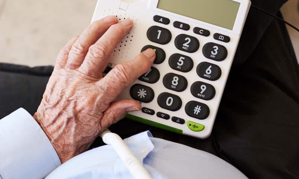 Älterer Mann an einem seniorengerechten Telefon