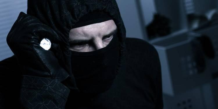 Einbrecher mit Sturmmaske und Taschenlampe