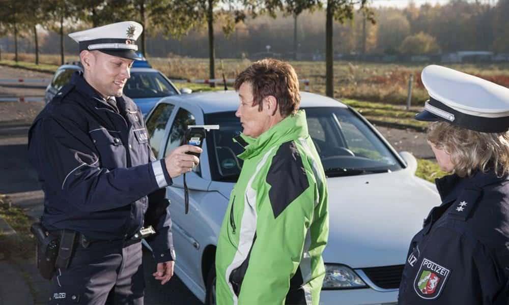 Zwei Polizisten führen einen Alkoholtest an einer Frau durch