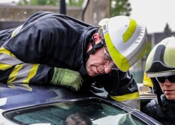 Feuerwehrmänner probieren eine eingeklemmte Person zu befreien