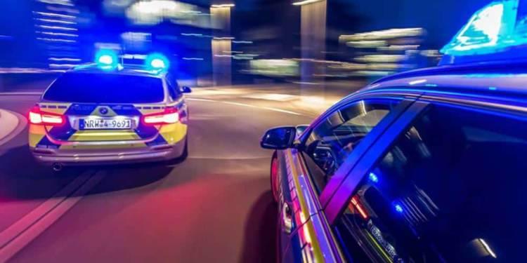 Zwei Streifenwagen fahren mit Blaulicht durch die Stadt