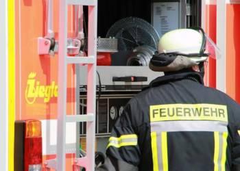Feuerwehrmann in Montur vor Feuerwehrauto
