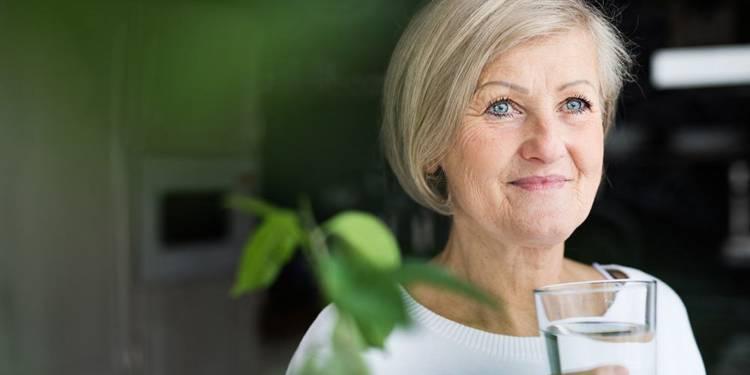 Frau hält ein Glas Wasser
