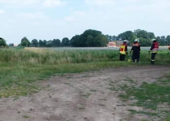 Der im Graben liegende Traktor wurde von dem hohen Gras verdeckt. Der Rettungshubschrauber landete rechts davon in unmittelbarer Nähe - © Polizei Rahden