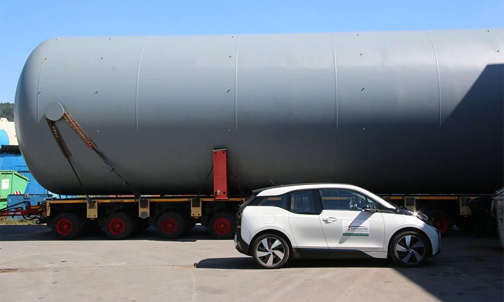 Größenvergleich Dienstfahrzeug Kreis Gütersloh, ein BMW i3, und der Tieflader mit dem rund 100 Tonnen schweren Behälter. - © Kreis Gütersloh