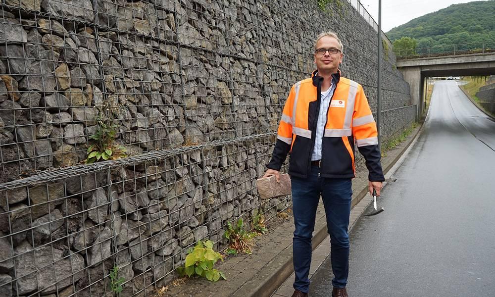 Thomas Hilker, der Leiter des Fachbereichs Planung im Eigenbetrieb Straßen des Kreises Lippe, zeigt eine Steinprobe des Materials, das bei der anstehenden Sanierung entlang der Kreisstraße 64 in Lügde verwendet wird. - © Kreis Lippe
