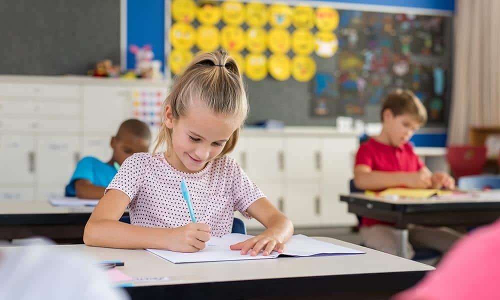 Junge Schülerin löst Aufgaben in der Schule
