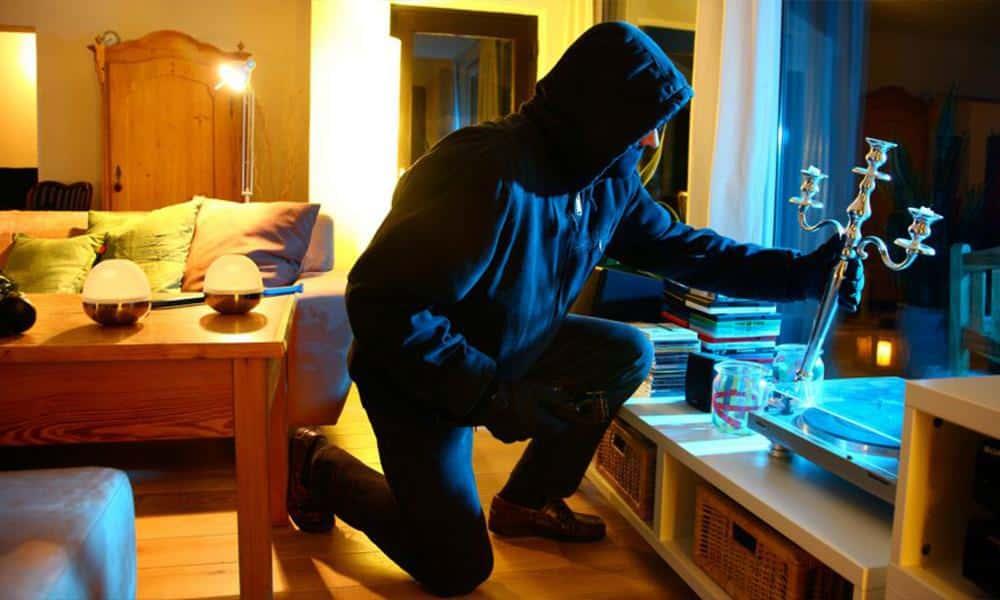 Vermummter Einbrechen mit Kerzenständer im Wohnzimmer