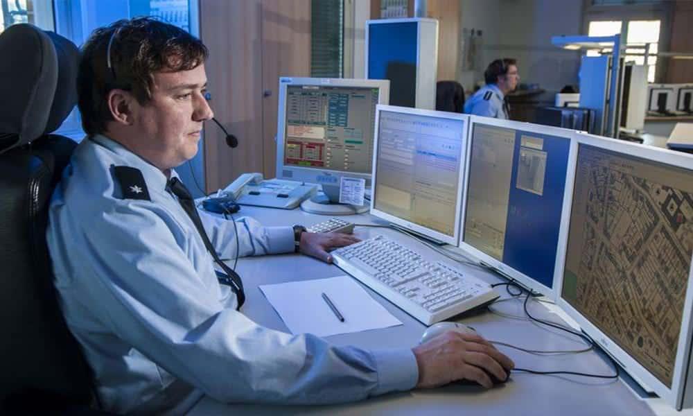 Polizist mit Headset vor mehreren Monitoren