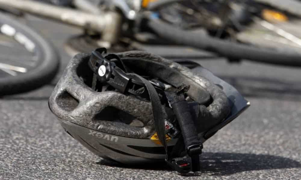 Fahrradhelm liegt vor Fahrrad auf der Straße