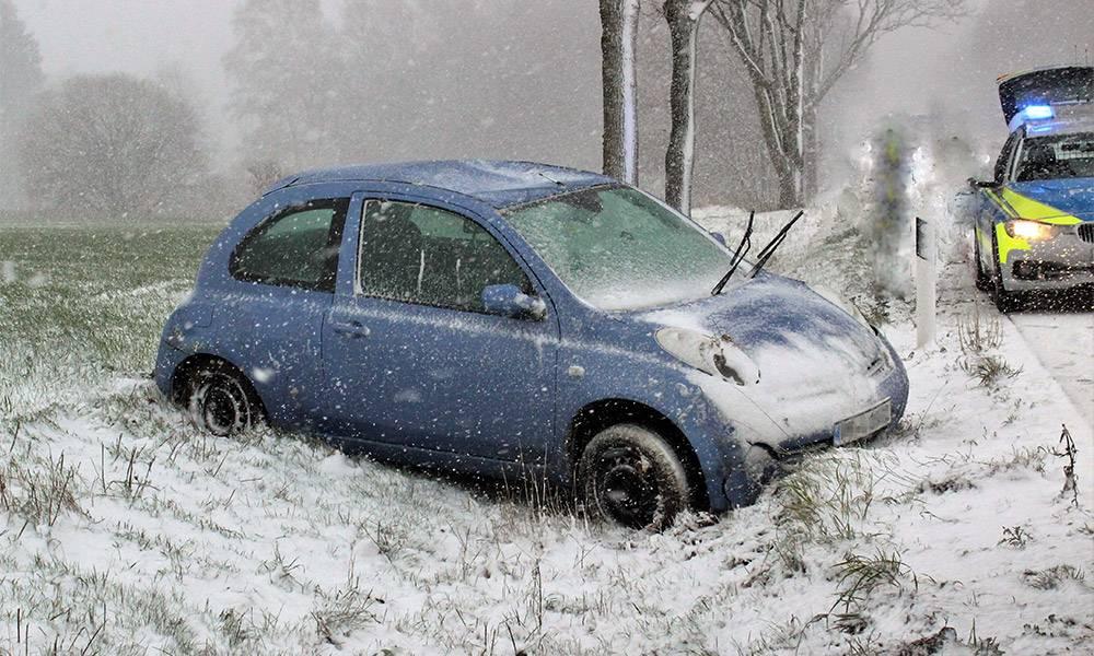 Kleinwagen nach Unfall auf verschneiter Straße