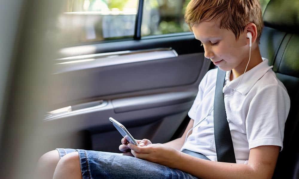 Lind mit Smartphone und Kopfhörern auf dem Rücksitz