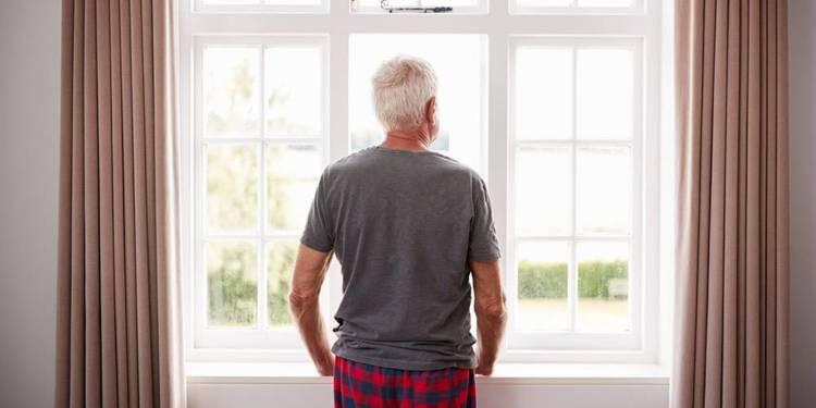 Mann mit grauen Haaren schaut aus dem Fenster