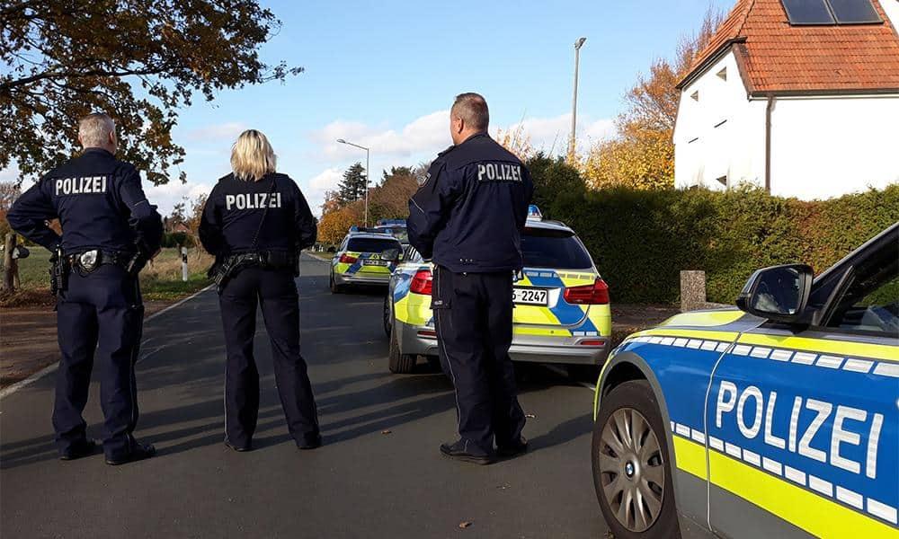 3 Polizisten und mehrere Polizeiautos