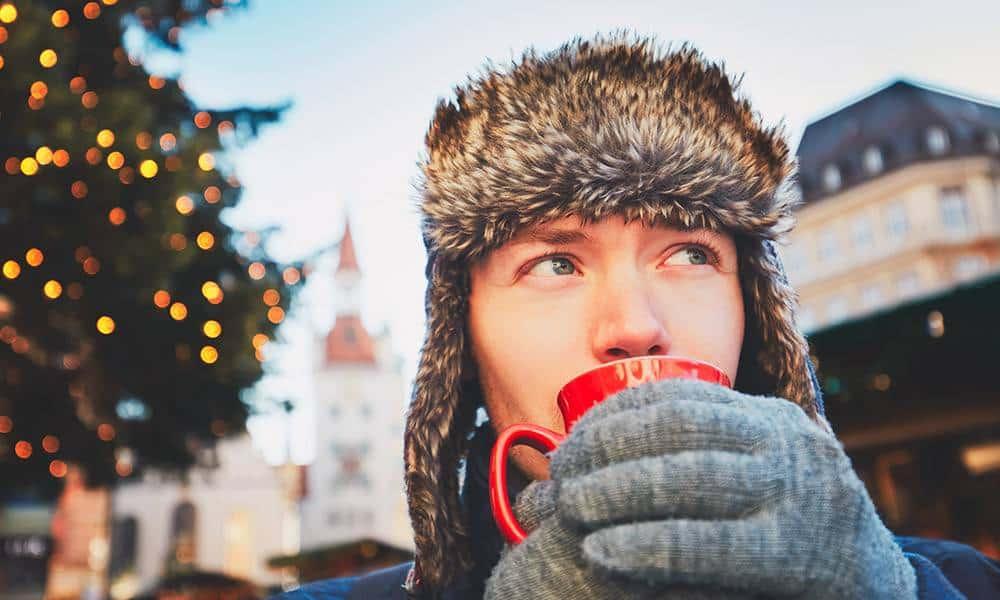 Junger Mann mit Mütze und Handschuhen trinkt Glühwein