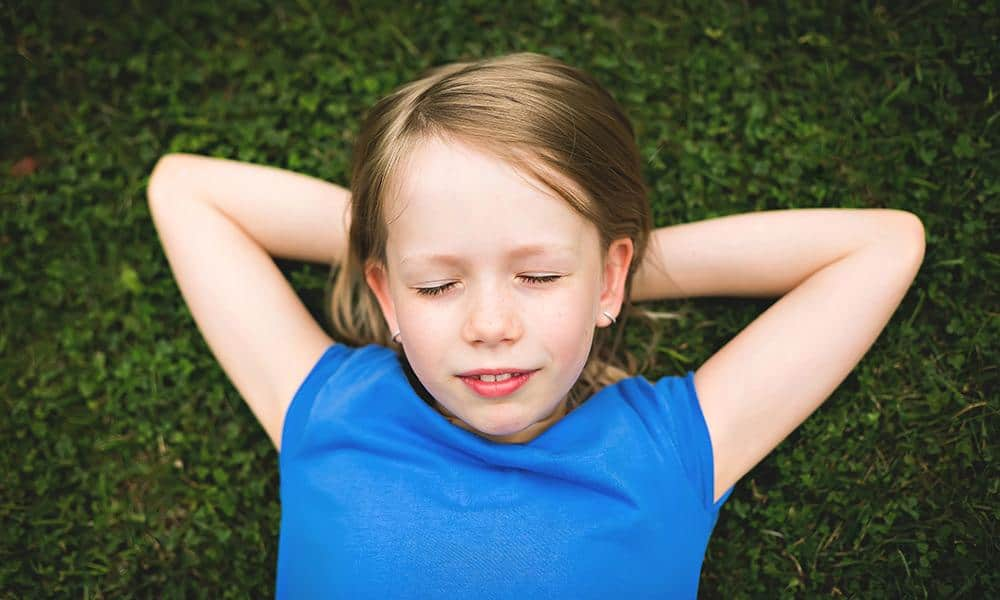 Mädchen liegt mit geschlossenen Auge auf einer Wiese