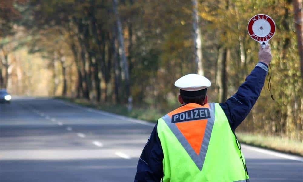 Polizist hält Auto mit einer Polizeikelle an