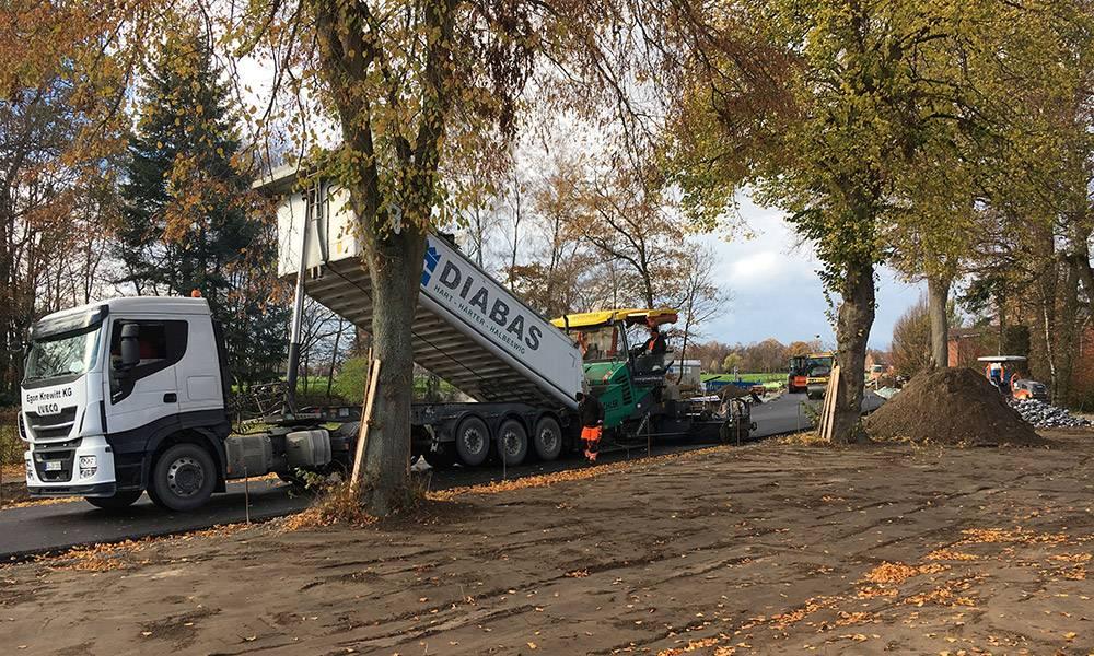 Der Fertiger wird per Lkw beladen, um die Asphaltschicht aufbringen zu können. - © Kreis Gütersloh