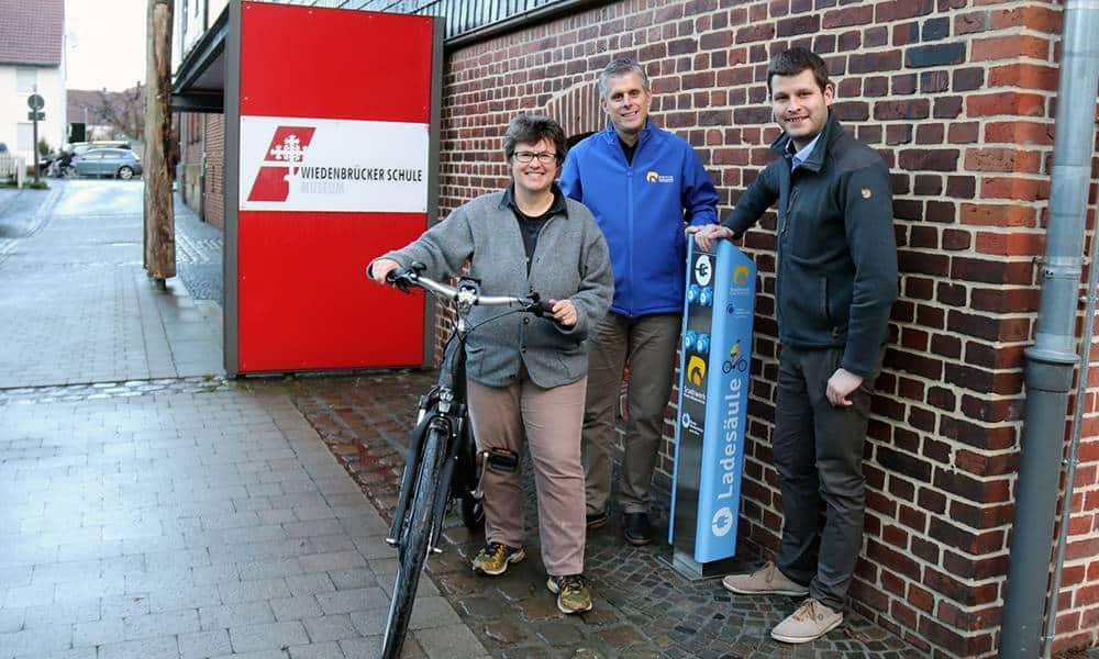 Museumsleiterin Christiane Hoffmann freut sich über die neue E-Bike-Ladesäule, die in Kooperation mit Stadtwerk-Geschäftsführer Torsten Fischer und Klimaschutzmanager Hans Fenkl aufgestellt wurde - © Stadt Rheda-Wiedenbrück