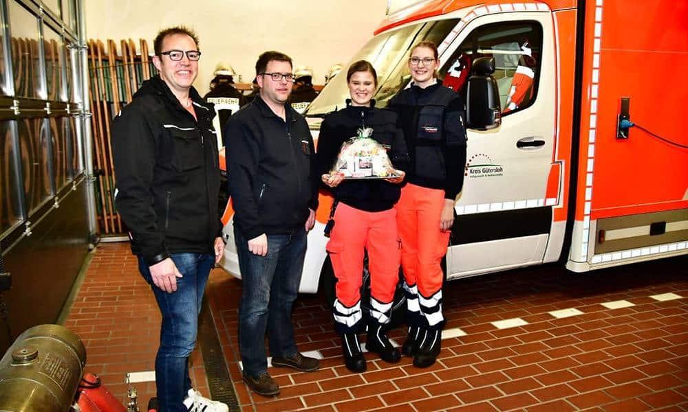 Die Löschzugführer Heiko Koenig (l.) und Peter Hagemann überraschten zusammen mit ihren Kameraden die Besatzung des neuen Rettungswagens, Justina Schmidt (2.v.r.) und Sina Kiewert, mit einem Präsent. - © Kreis Gütersloh