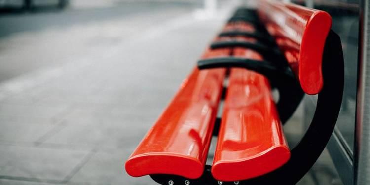 Rote Sitzbank einer Bushaltestelle