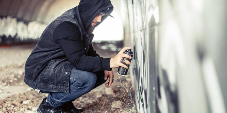 Junger Mann beim Graffiti in einer Unterführung