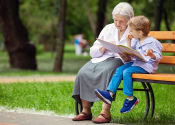 Großmutter liest mit Enkel auf einer Bank
